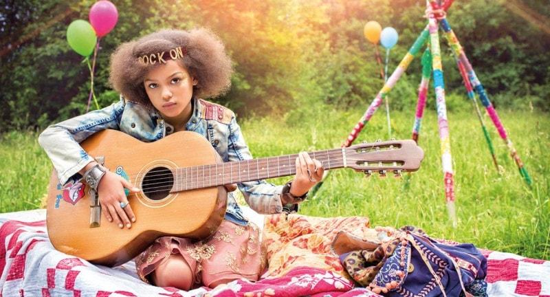 girl wearing headband playing guitar festival fashion shoot