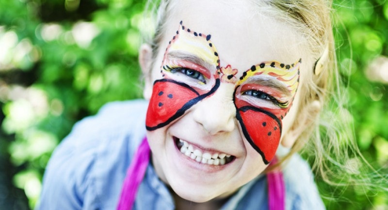 little girl with butterfly face paint at the geronimo festival