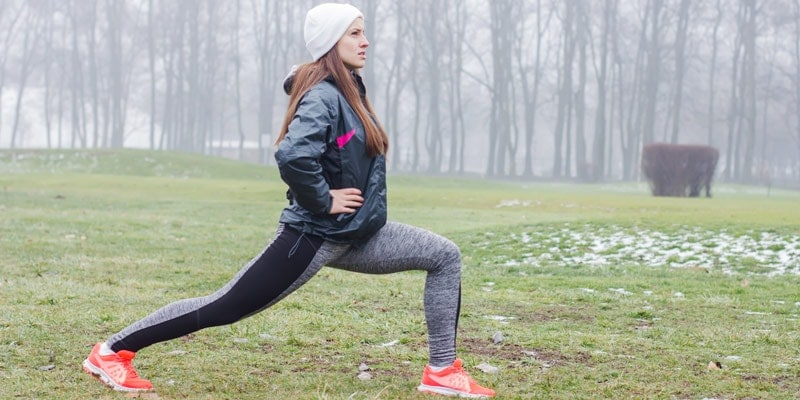 woman-exercising-in-the-park-lunging-in-the-snow