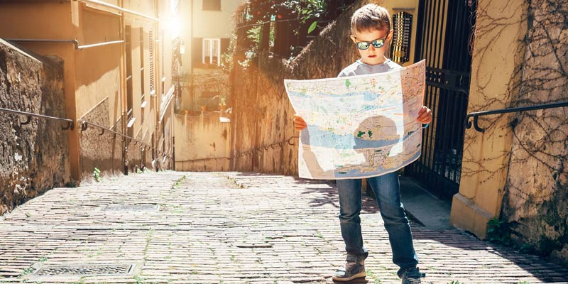 little-boy-looking-at-map-on-old-street-in-itlay