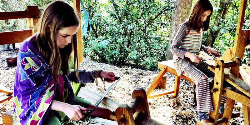 Two girls using traditional woodworking skills at Forest Garden, Sussex