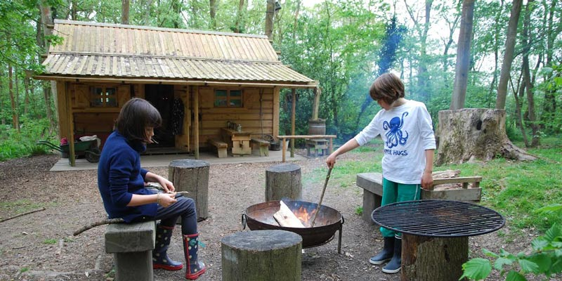 Idaho Cabin in the Sussex woods with two children around a fire pit