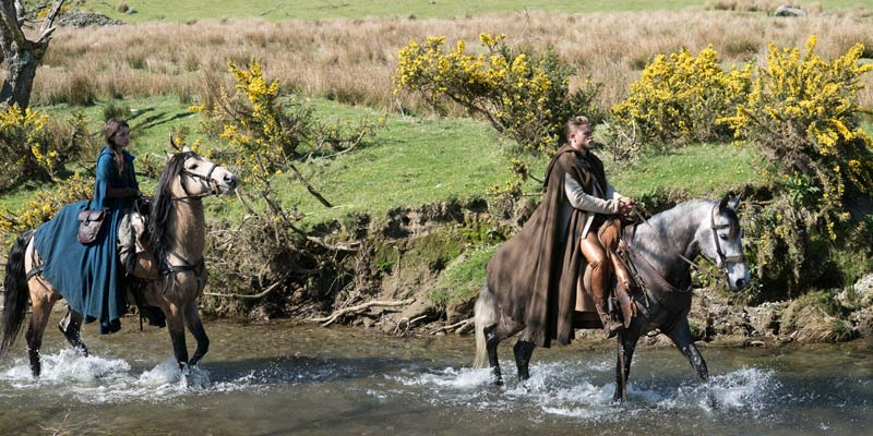 A still from King Arthur: Legend of the Sword in Gwyant, Snowdonia with a man and a woman on horseback in the river