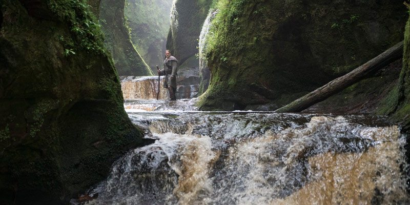 Charlie Hunnam as King Arthur standing on a rock in the river at the Devils Pulpit Finnich Glen, Killearn, Scotland