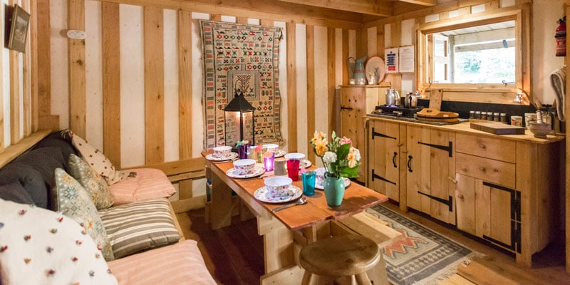 Idaho log cabin interior with wooden kitchen, dining table and rugs