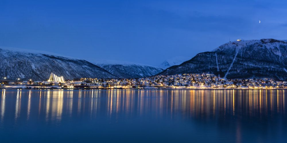 Tromso Norway city lights and mountains under a winter evening sky