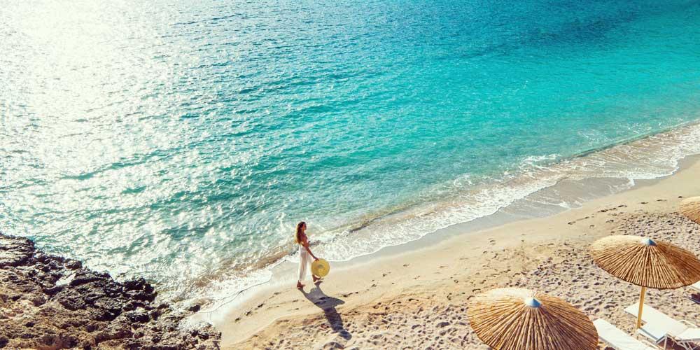 Woman beach walk summer savings