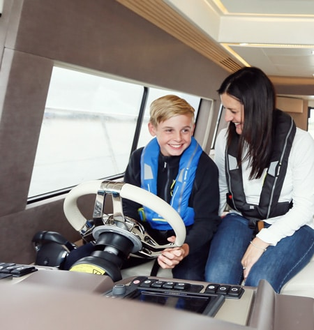 boy steering boat with woman RYA training courses