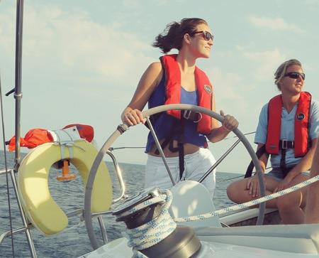 Woman steering a ship RYA training courses