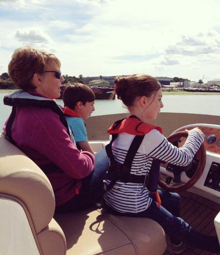 Family kids steering boat RYA training courses