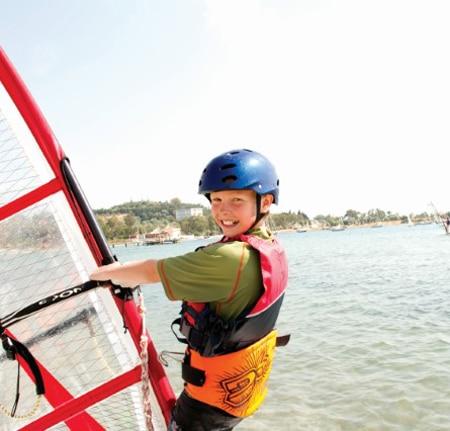 Boy smiling windsurfing RYA training courses
