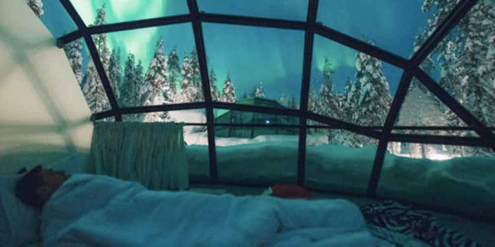 Man sleeping in Glass Igloo Village, Finland