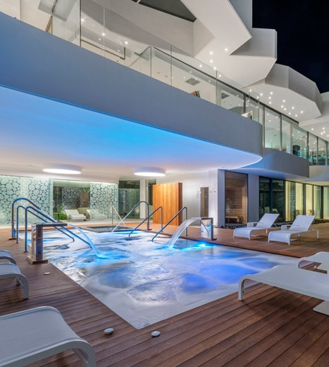 A spa pool with water jets on and loungers around it on a wooden deck