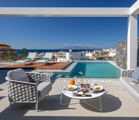 A private terrace with a deck, sun loungers, a pool, chairs and food on a table with the ocean in the background