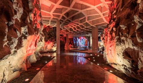 An underground walkway with red lights illuminating the rock walls and ceiling