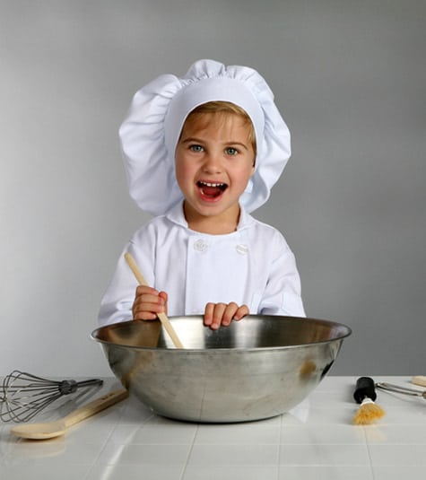 A young person in white chef's whites with a metal bowl and utensils on the counter