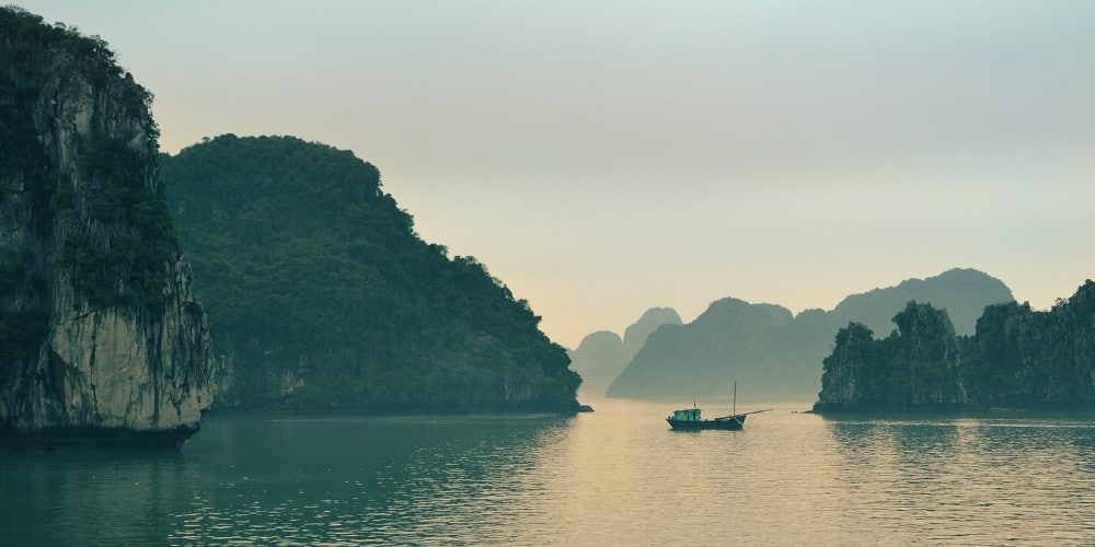 Hu Long Bay Vietnam limestone karsts and junk at dawn