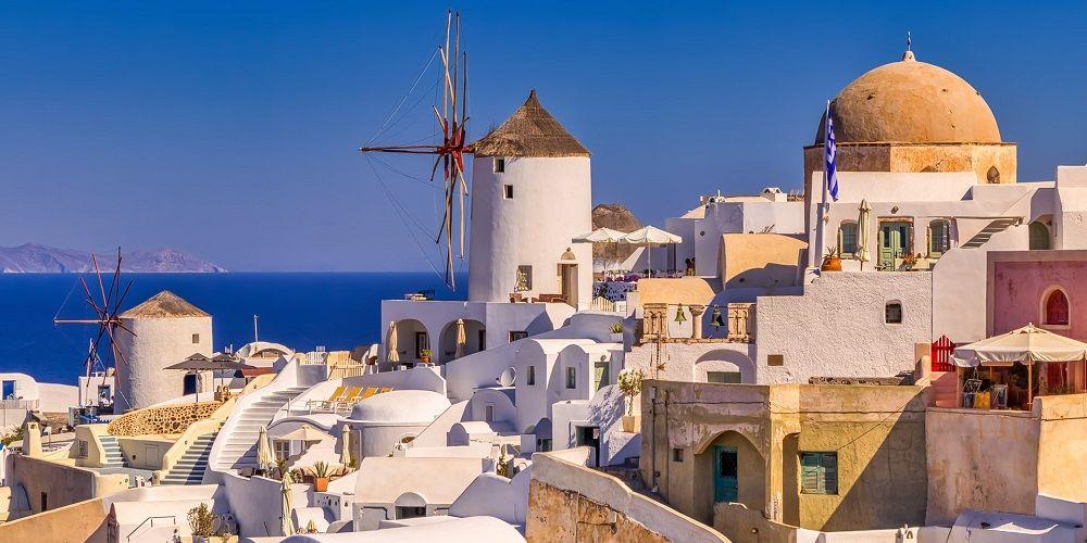whitewashed Santorini town edge of Caldera blue skies