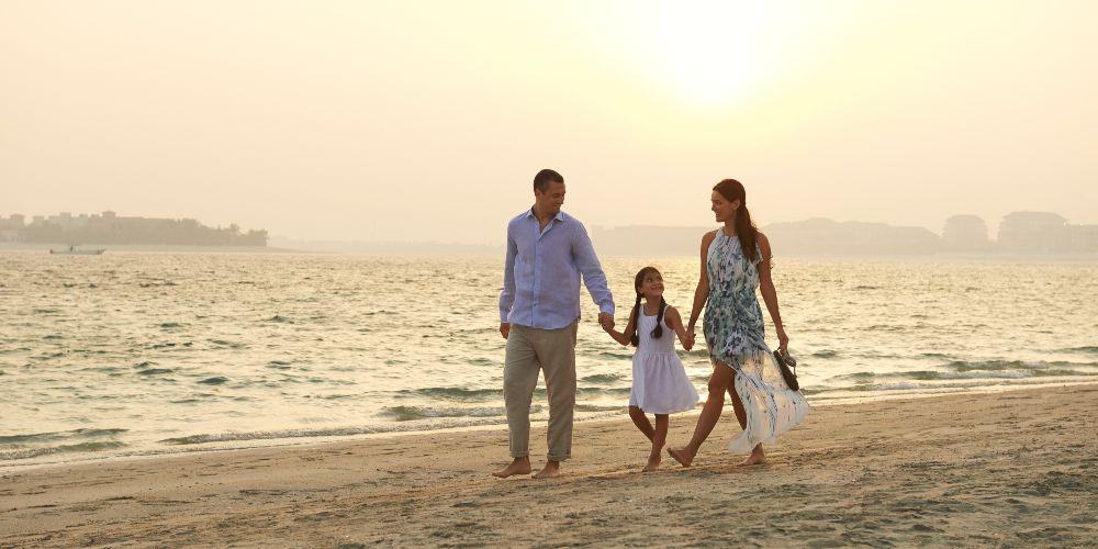 Dubai family holidays family walking on Dubai beach at sunset